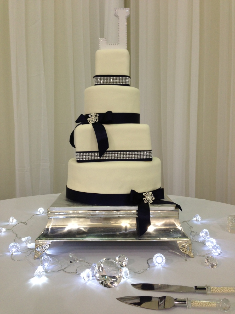 """Lauren""  Square and round tiered wedding cake with navy and rhinestone ribbon accents."