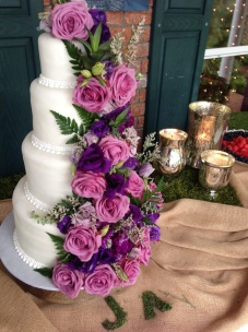 """Audrey"" Simple white wedding cake with lush purple flower cascade."