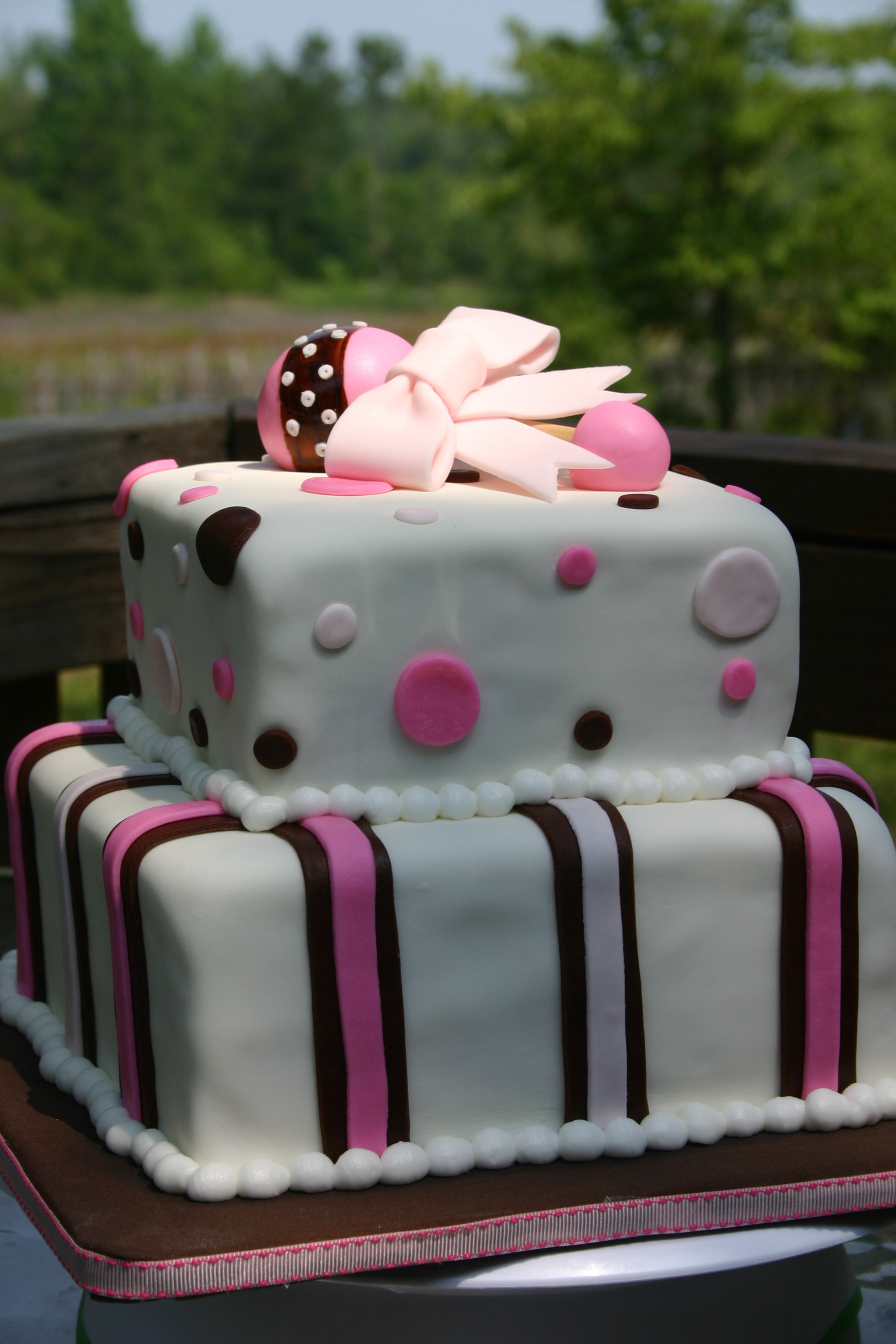 Baby shower cake in pink and brown with rattle