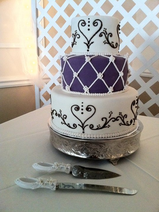 3 tier wedding cake in ivory purple and brown featuring royal icing lattice
