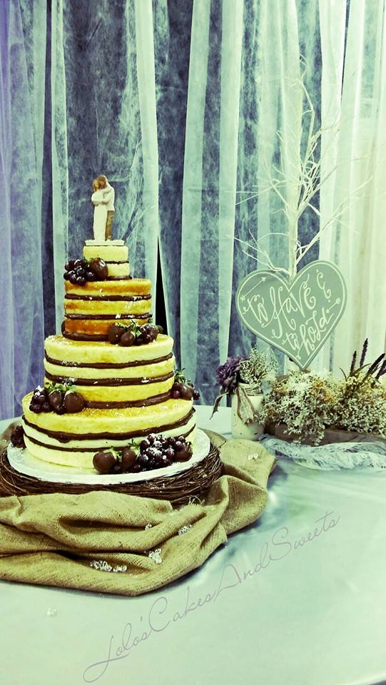 """""""Nancy"""" naked wedding cake adorned with fruit and sugar sprinkled."""
