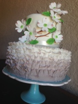 """Stacey"" Ombre ruffle wedding cake in taupe with dogwood flowers."