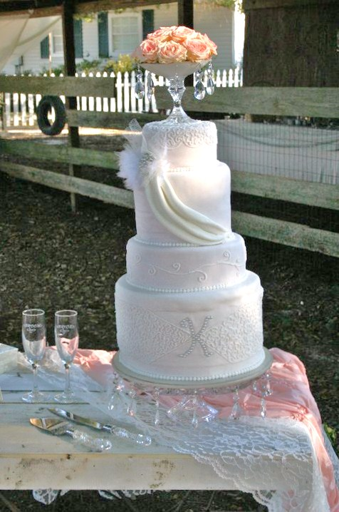 pale pink vintage wedding cake with draping spanish lace monogram and