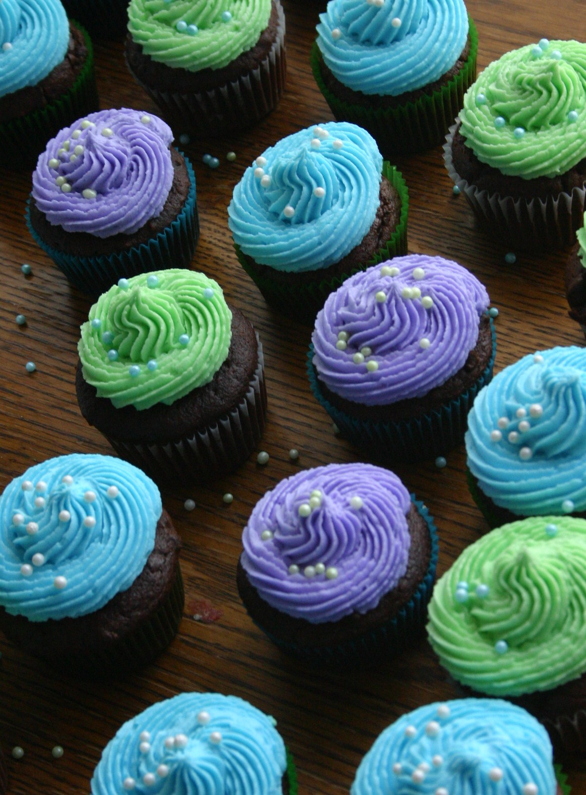 Purple blue and green cupcakes with white nonpareil