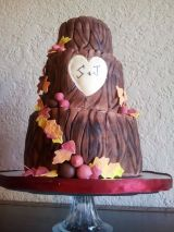 """Autumn"" Tree stump wedding cake with heart and carved initials. Autumn leaves and acorn swag."