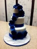 """Malia"" Morning glory inspired, this cake features deep blue gumpaste flowers and blue satin ribbon."