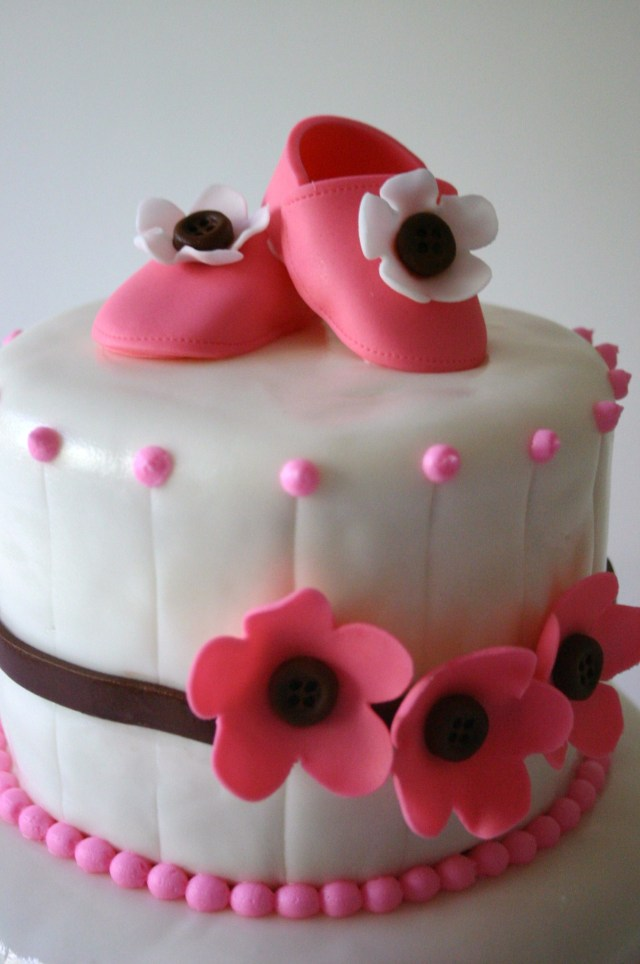 Close up of gumpaste booties on pink and brown baby shower cake