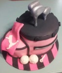 Pink golf bag with Puma hand towel, hand crafted golf balls, clubs and tee on top of a fondant covered cake board. Feeds 20-25. MSRP $125