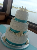"""Jessica"" 3 tier white wedding cake with seashells, swirls, & aqua ribbon border. Photo taken aboard a cruise boat in the harbor of the Village of Baytowne Wharf in SanDestin, FL."