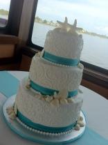 """Jessica"" 3 tier white wedding cake with seashells, swirls, & aqua ribbon border. Photo taken aboard a cruise boat in the harbor of the Village of Baytowne Wharf in SanDestin, FL."