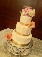 """Miranda"" Ivory wedding cake with ivory accents and champagne ribbon border on silver cake stand"