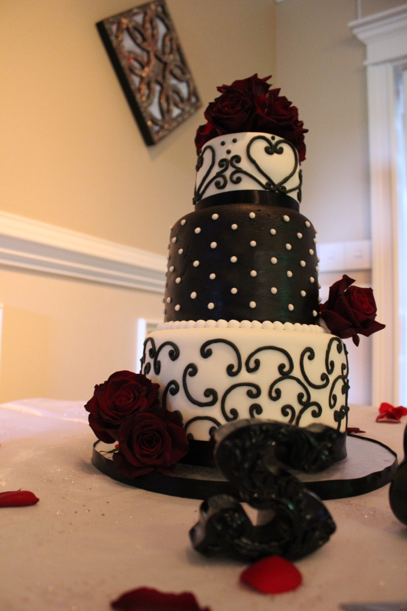 """Sherrill"" Black & white 3 tier wedding cake with red roses - Photo taken at the reception venue of the Compass Rose in Niceville, FL"