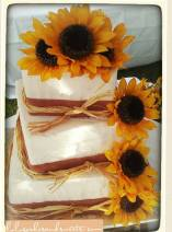 """April"" Country Chic sporting burlap ribbon made of fondant, sunflowers, and straw."